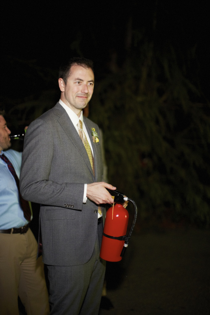The groom stands by with a fire extinguisher