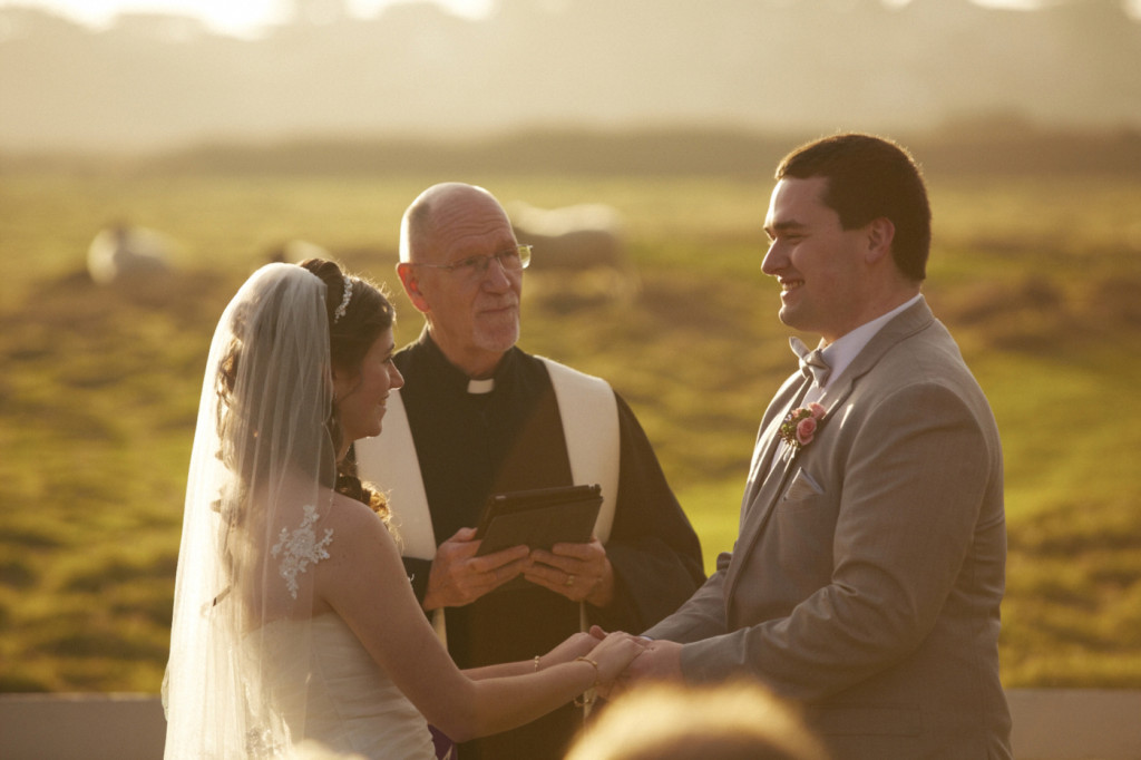 The sun sets behind the wedding couple