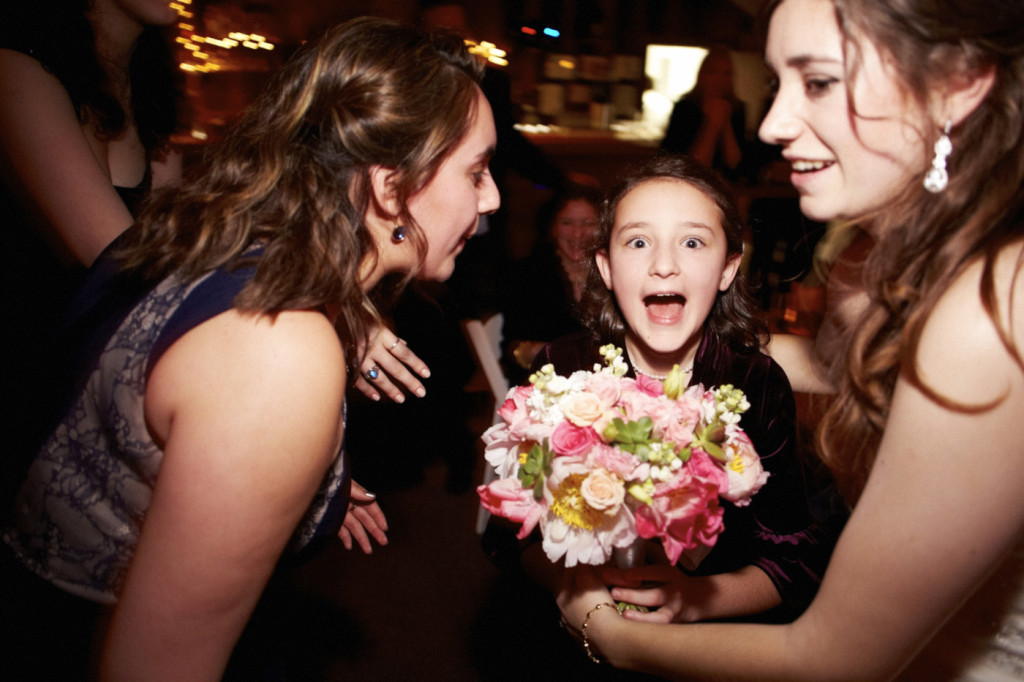 The flower girl is shocked that the bouquet is being given to her.