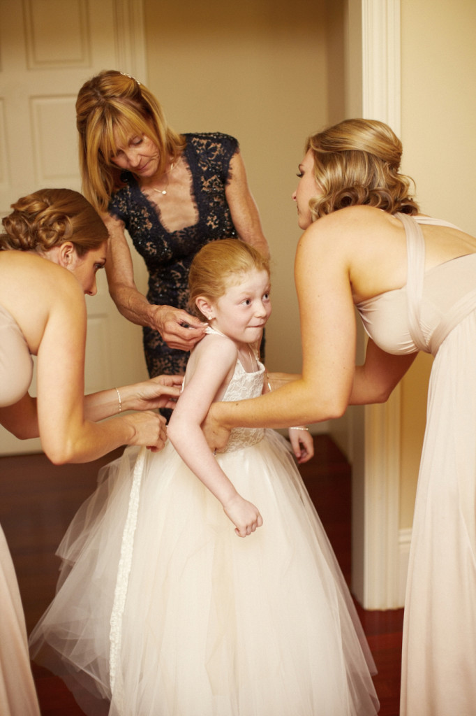 Bridesmaids and the mother of the bride help the flower girl get in her dress