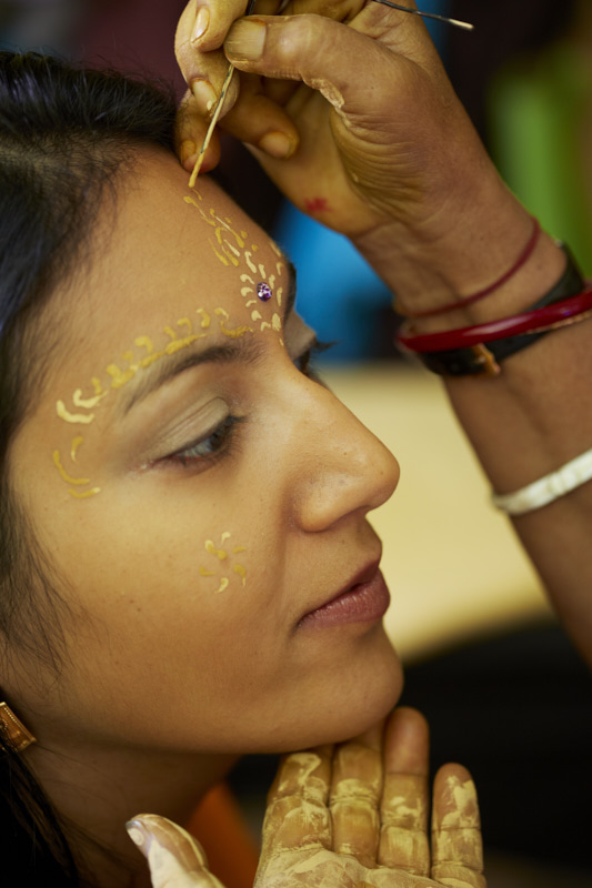Sandalwood paste is used to paint decorations on the bride's face.