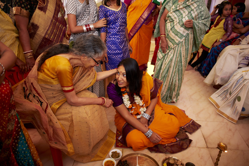 The bride's mother feeds her bites of the feast.