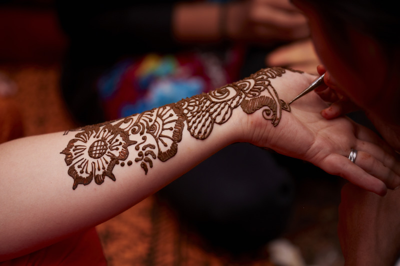 A mehndi artist applies henna to the guests.
