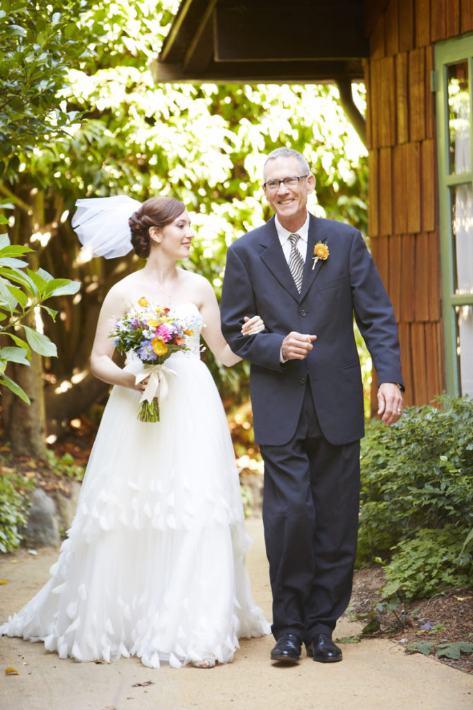 The bride and her father come down the path.