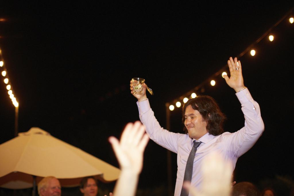 The groom is raised up on the dance floor